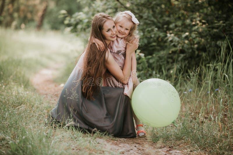 Mooie moeder en haar weinig dochter in openlucht nave Openluchtportret van gelukkige familie De gelukkige Vreugde van de Moeder`  royalty-vrije stock fotografie