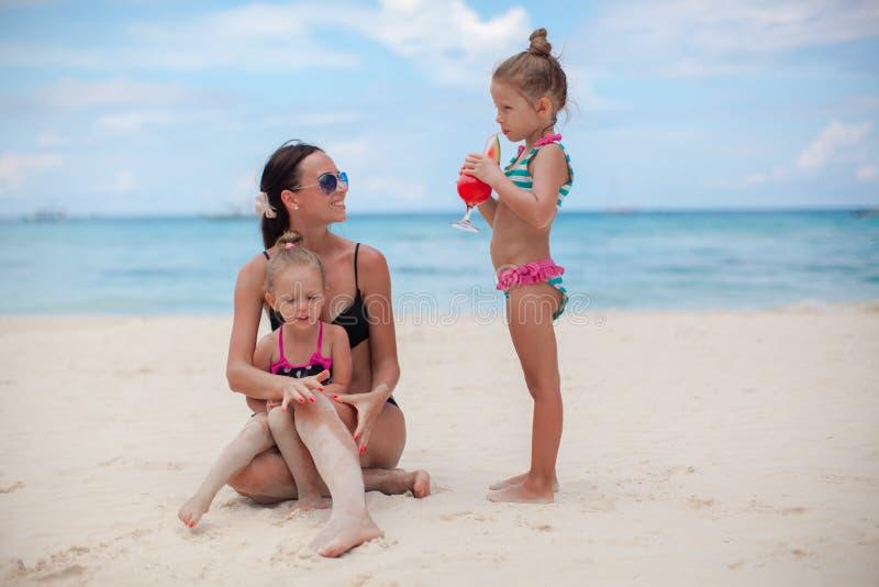 Mooie moeder en twee haar jonge geitjes bij exotisch strand stock afbeelding