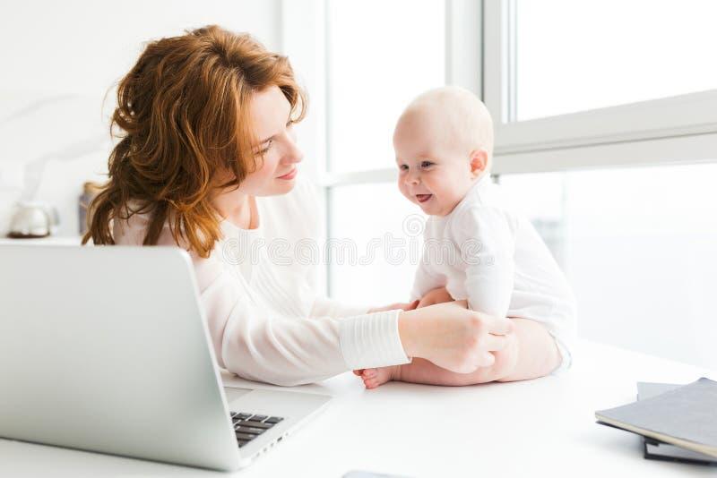Mooie moeder zitting en dreamily dichtbij het bekijken haar gelukkige kleine baby met laptop stock foto's