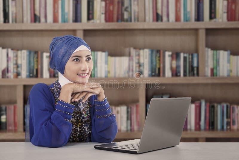 Mooie moslimmeisjesstudie met laptop bij bibliotheek stock foto