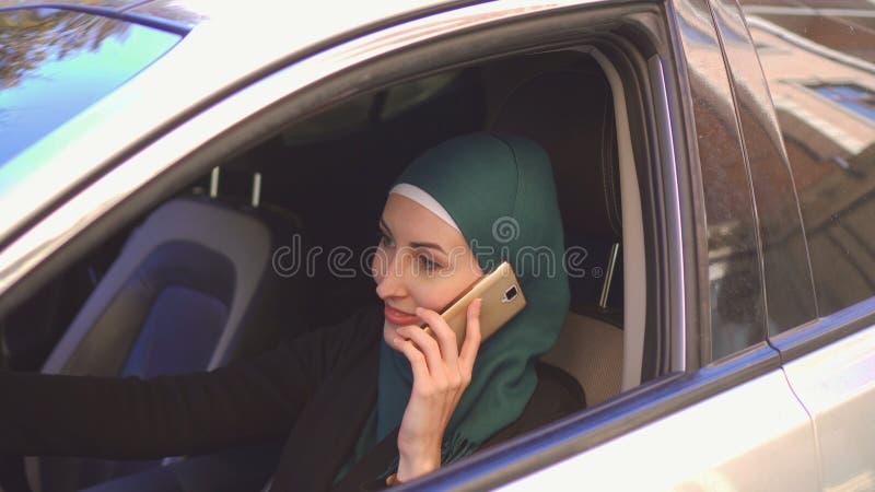 Mooie moslimvrouw die een auto drijven die op telefoon het glimlachen spreken royalty-vrije stock fotografie