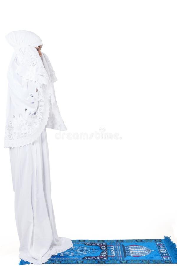Mooie moslimvrouw die op geïsoleerd tapijt bidden - royalty-vrije stock foto