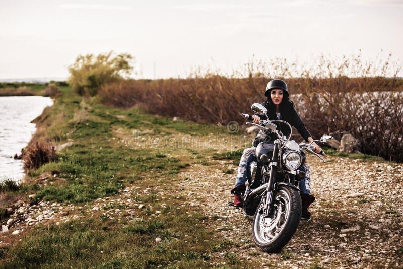 Mooie motorfiets donkerbruine vrouw met een klassieke motorfiets c stock afbeelding
