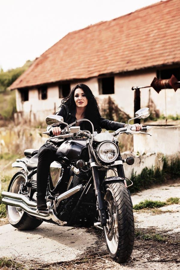 Mooie motorfiets donkerbruine vrouw met een klassieke motorfiets c stock foto