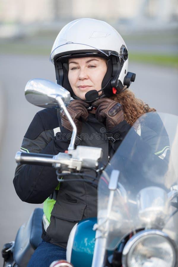 Mooie motorrijder Kaukasische vrouw die op witte helm proberen terwijl het zitten op fiets en het bekijken achterspiegel stock afbeelding