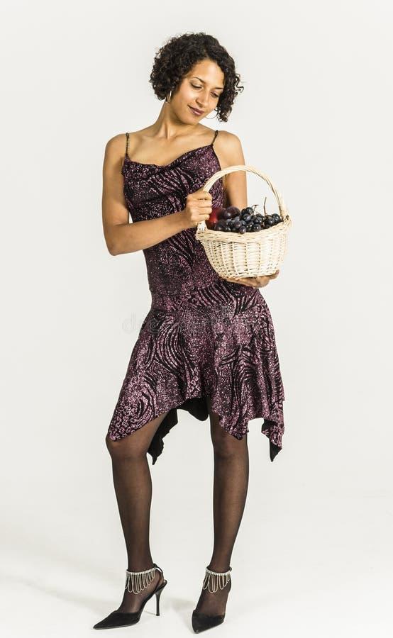 Mooie mulatvrouw in een cocktailkleding met een mand fruit royalty-vrije stock afbeelding