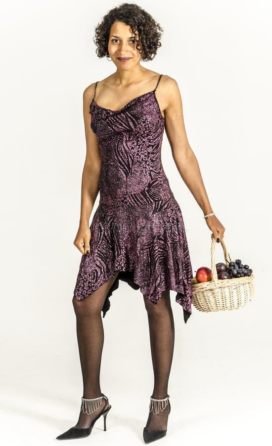 Mooie mulatvrouw in een cocktailkleding met een mand fruit stock foto's