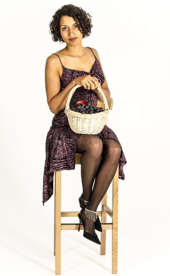 Mooie mulatvrouw in een cocktailkleding met een mand fruit stock foto