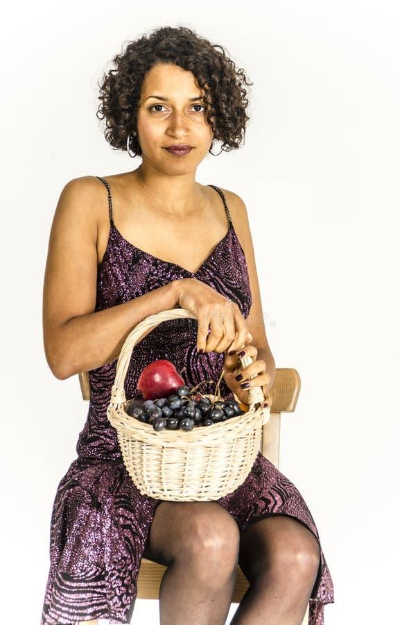 Mooie mulatvrouw in een cocktailkleding met een mand fruit stock afbeeldingen