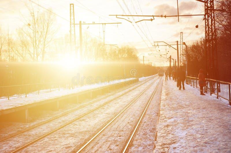 Mooie multicolored bewolkte hemel tijdens een heldere oranje zonsondergang Spoorpassen door de dorpsaanplantingen Russisch spoorw royalty-vrije stock foto's
