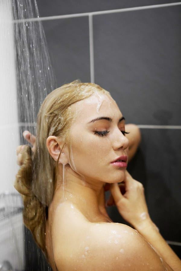 Mooie naakte jonge vrouw die douche in badkamers nemen stock afbeeldingen