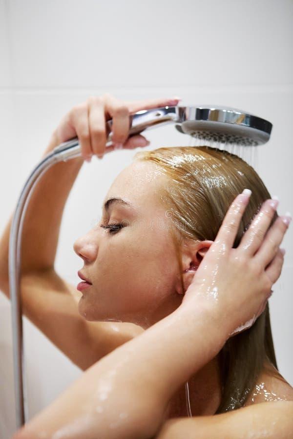 Mooie naakte jonge vrouw die douche in badkamers nemen royalty-vrije stock fotografie