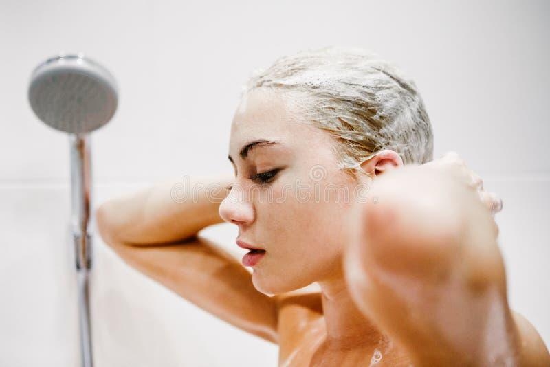 Mooie naakte jonge vrouw die douche in badkamers nemen stock foto
