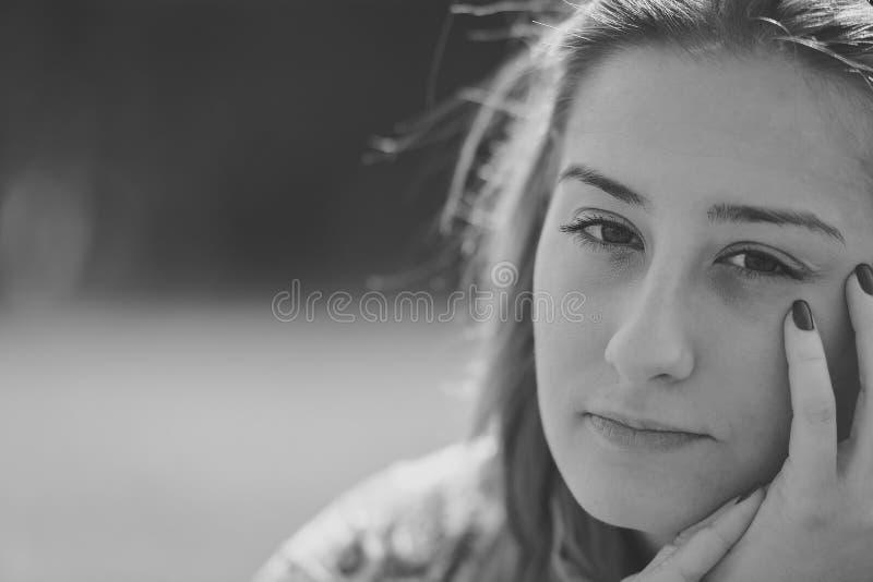 Mooie nadenkende jonge vrouw in het park op een warme de zomerdag stock afbeeldingen