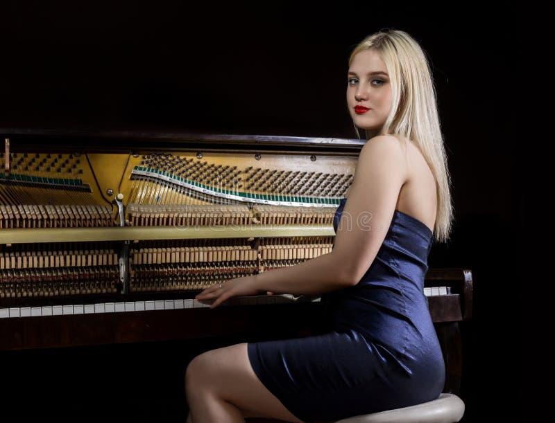 Mooie nadenkende meisjeszitting dichtbij piano op een donkere achtergrond royalty-vrije stock afbeelding
