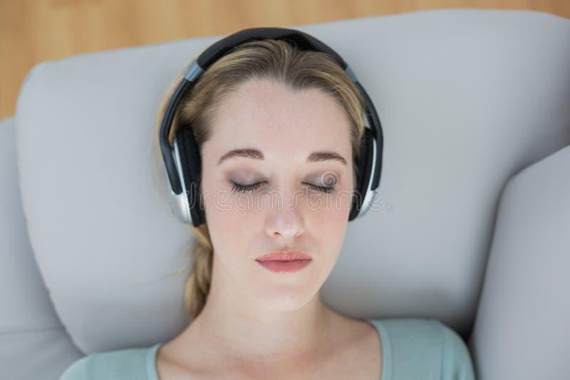 Mooie natuurlijke vrouw die met hoofdtelefoons aan muziek luisteren die liggen royalty-vrije stock foto's