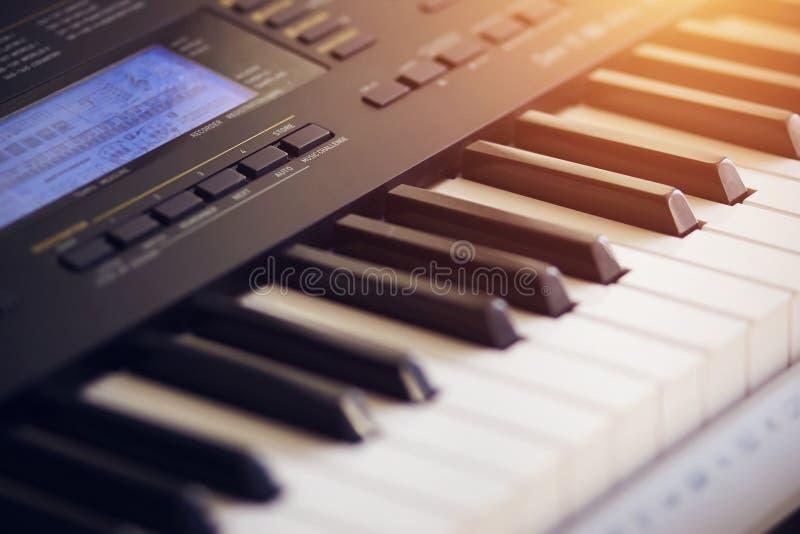 Mooie nieuwe synthesizer die door de oranje stralen wordt verlicht stock fotografie