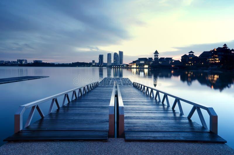 Mooie ochtend tijdens blauw uur bij Putrajaya-Oever van het meer, Maleisië hotel en de bouwbezinning over het meer houten en mode royalty-vrije stock foto