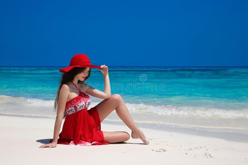 Mooie onbezorgde vrouw die in hoed op exotische overzees, brunette genieten van royalty-vrije stock afbeeldingen