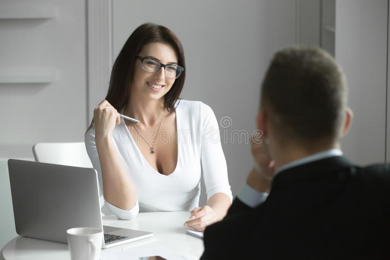 Mooie onderneemster die aan een mannelijke baankandidaat spreken stock foto's