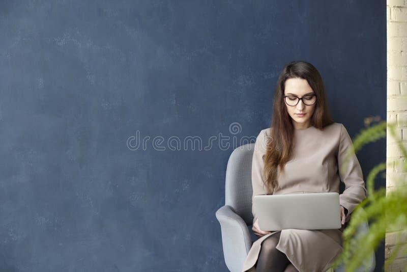 Mooie onderneemster die aan laptop werken terwijl het zitten in modern zolderbureau Donkerblauwe muurachtergrond, daglicht royalty-vrije stock afbeelding