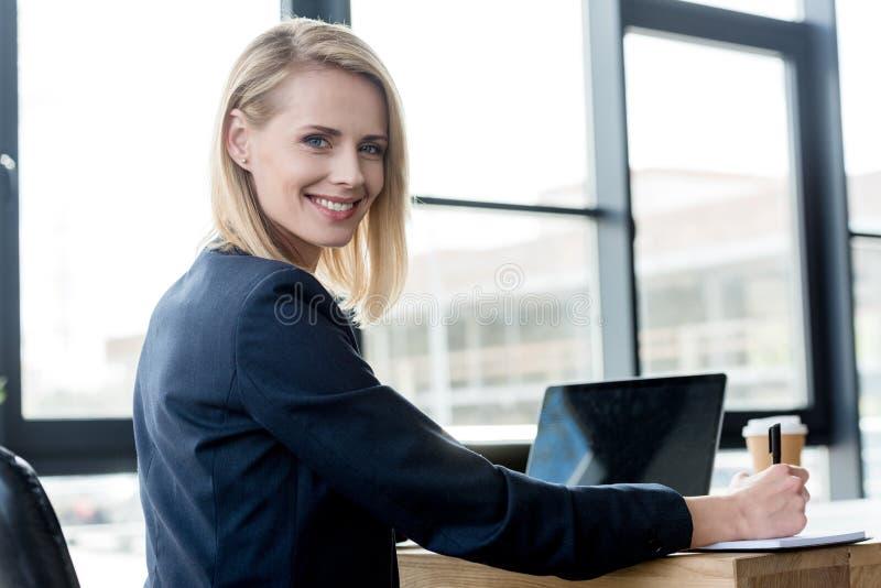 mooie onderneemster die bij camera glimlachen terwijl het gebruiken van laptop en het nemen van nota's stock fotografie