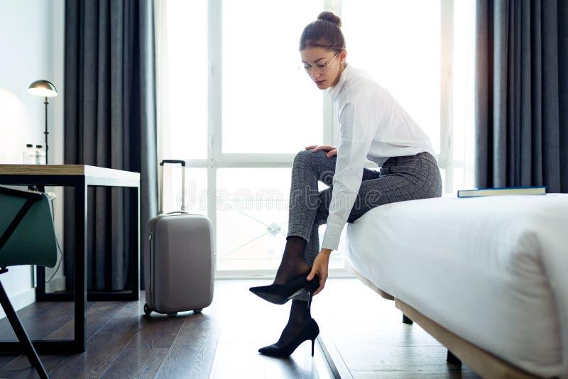 Mooie onderneemster die hoge hielenschoenen na het werk opstijgen bij haar hotelruimte royalty-vrije stock foto
