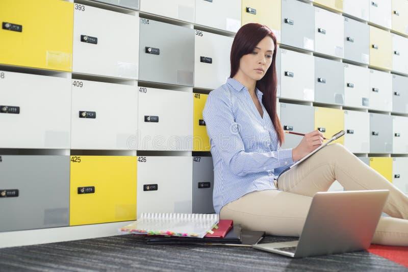 Mooie onderneemster die laptop met behulp van terwijl het schrijven in kleedkamer op creatief kantoor stock afbeeldingen
