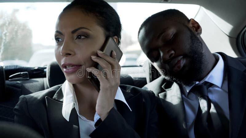 Mooie onderneemster die op telefoon in auto, mens spreken die met dame, minnaars flirten stock foto