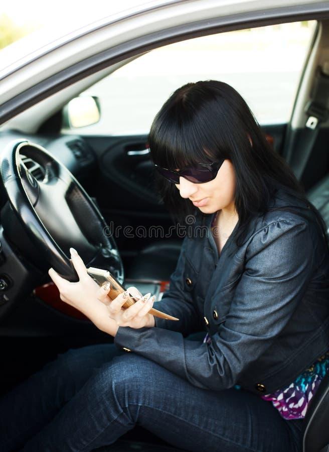 Mooie onderneemster in haar auto na het werk stock foto's