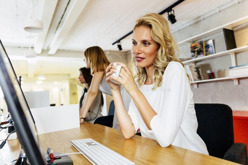Mooie onderneemster het drinken koffie om waakzaam te blijven royalty-vrije stock afbeelding