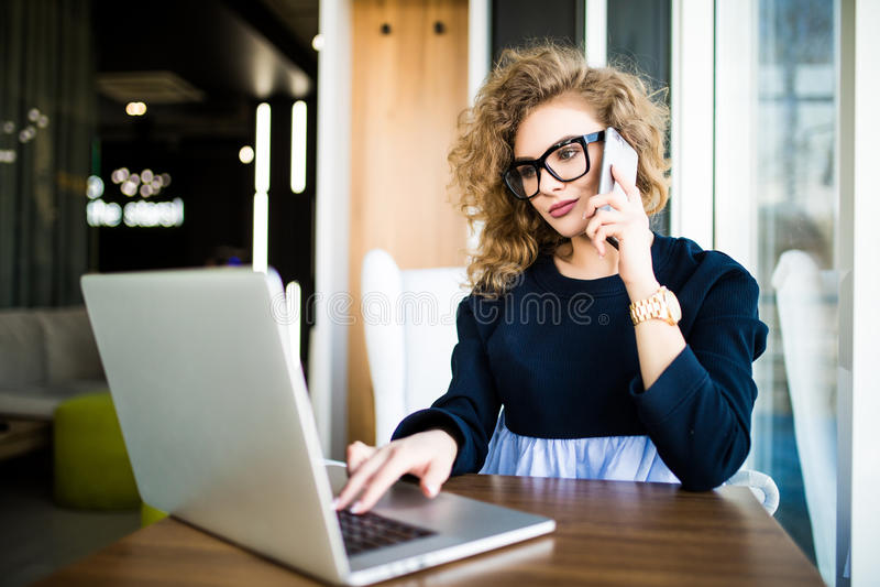 Mooie onderneemster het werk zitting bij haar bureau in het bureau Bekijk laptop stock foto's