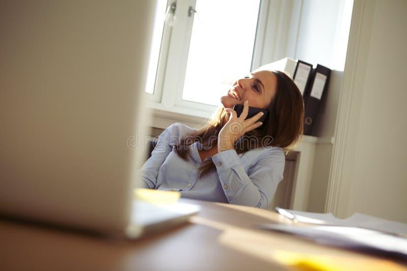 Mooie onderneemster in huisbureau die op mobiele telefoon spreken royalty-vrije stock fotografie