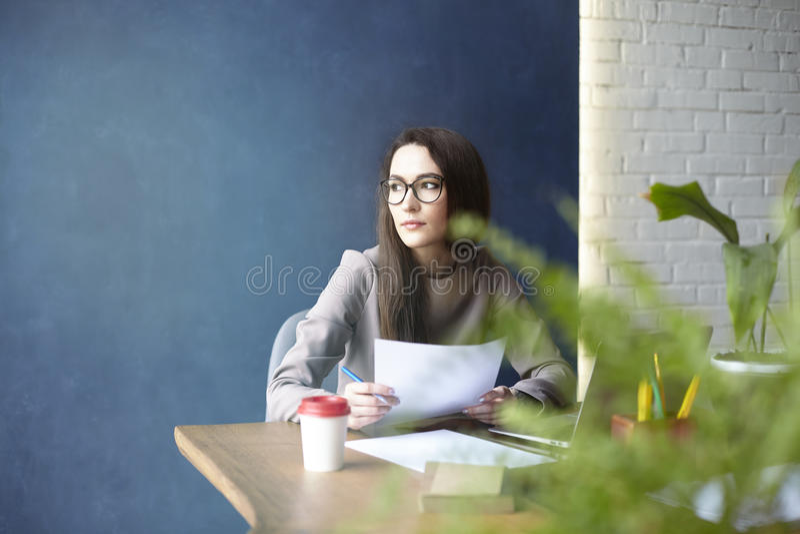 Mooie onderneemster met lang haar die met documentatie, blad, laptop werken terwijl het zitten in modern zolderbureau stock foto