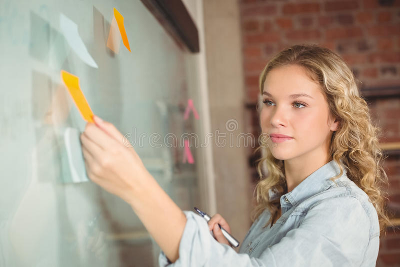 Mooie onderneemster plakkende nota's aan boord in bureau stock afbeelding