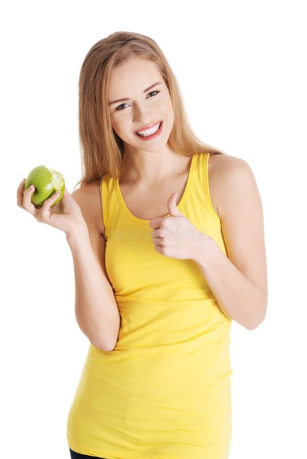 Mooie oorzakelijke Kaukasische vrouw die verse groene appel houden met royalty-vrije stock foto's