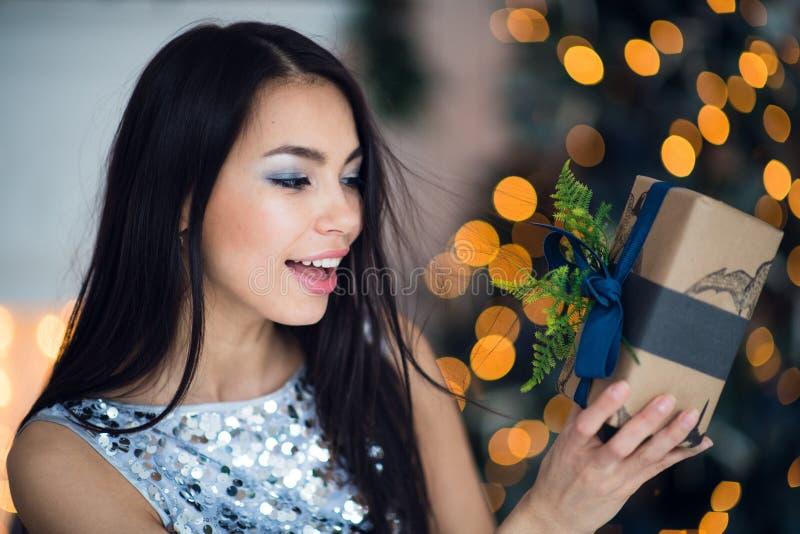 Mooie opgewekte glimlachende jonge vrouw die met huidige gift gelukkige dichtbijgelegen Kerstmisboom voelen De gelukkige jonge za stock foto's