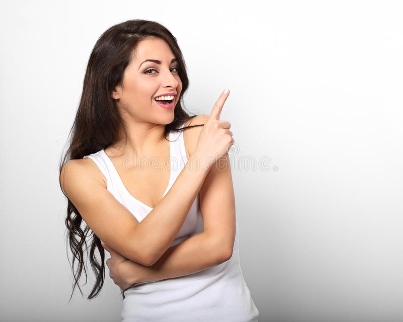 Mooie opgewekte toevallige vrouw die de vinger en smilin benadrukken stock foto