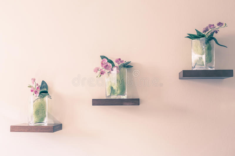 Mooie orchidee in glasvaas op plank stock fotografie