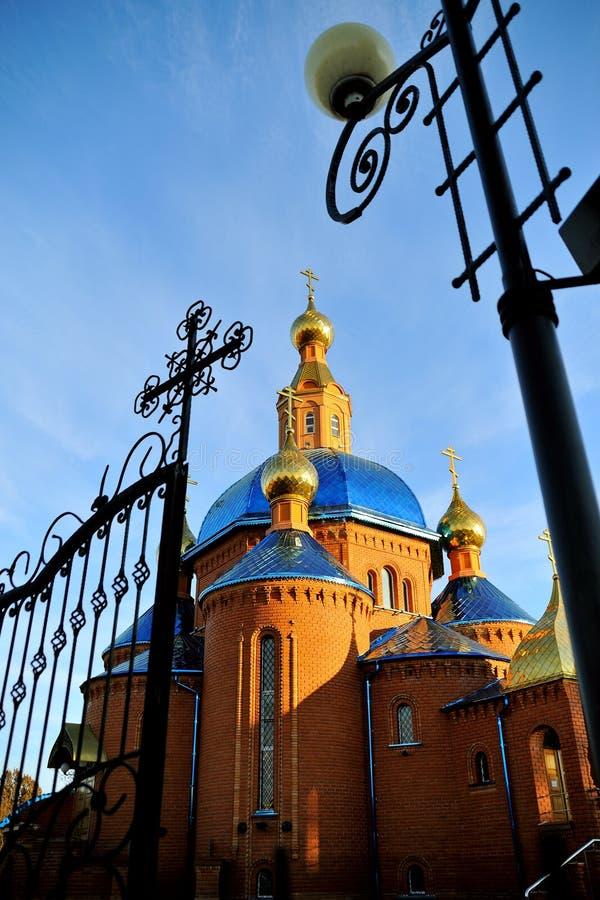 Mooie Orthodoxe Kerk van rode baksteen met een blauw dak, met Gouden koepels bij zonsondergang Rusland, Belgorod Algemene verschi stock fotografie