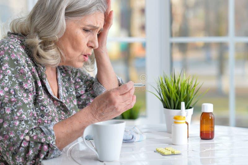 Mooie oude vrouw die pillen nemen stock afbeeldingen
