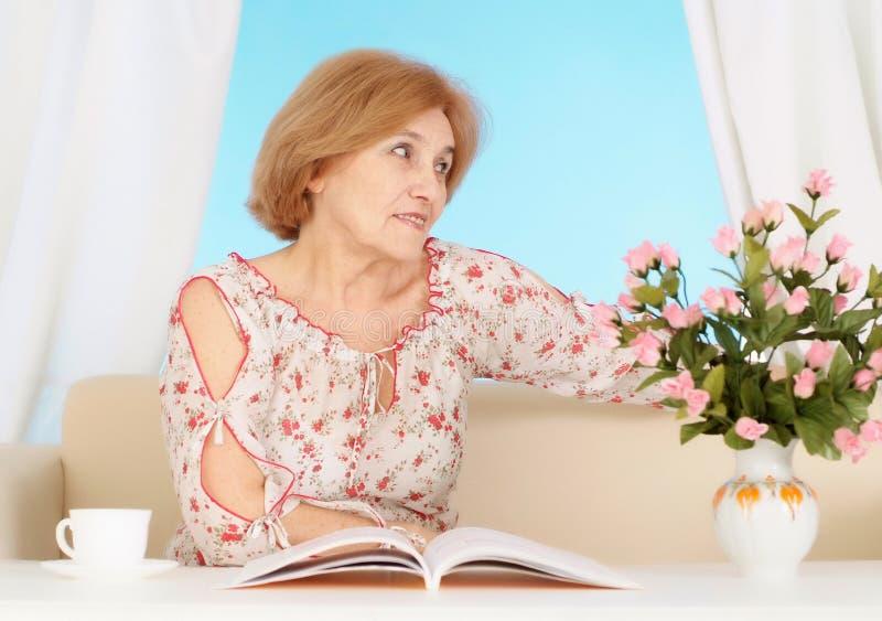 Mooie oudere vrouw die in de slaapkamer rusten stock foto