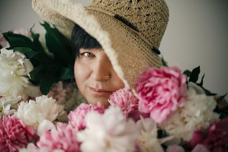 Mooie oudere vrouw in hoed het stellen met vele pioenbloemen Gelukkige moeder met groot boeket van roze pioenen van kinderen gelu stock fotografie