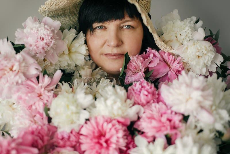 Mooie oudere vrouw in hoed het stellen met vele pioenbloemen Gelukkige moeder met groot boeket van roze pioenen van kinderen gelu stock foto's