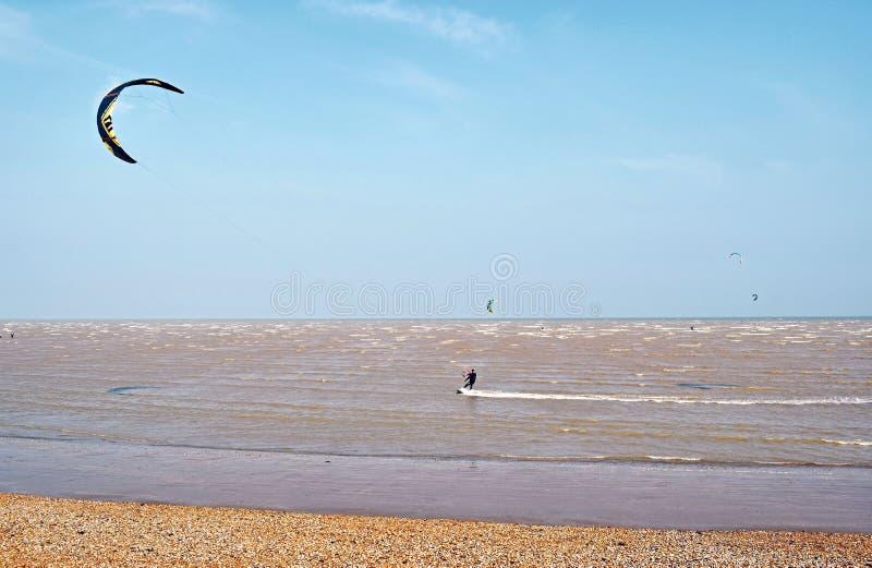 Mooie overzeese mening met mensen die watersporten op een winderige dag doen stock foto's