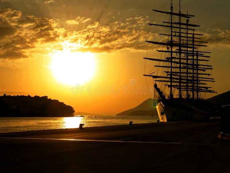 Mooie overzeese zonsondergang met oud schip stock fotografie
