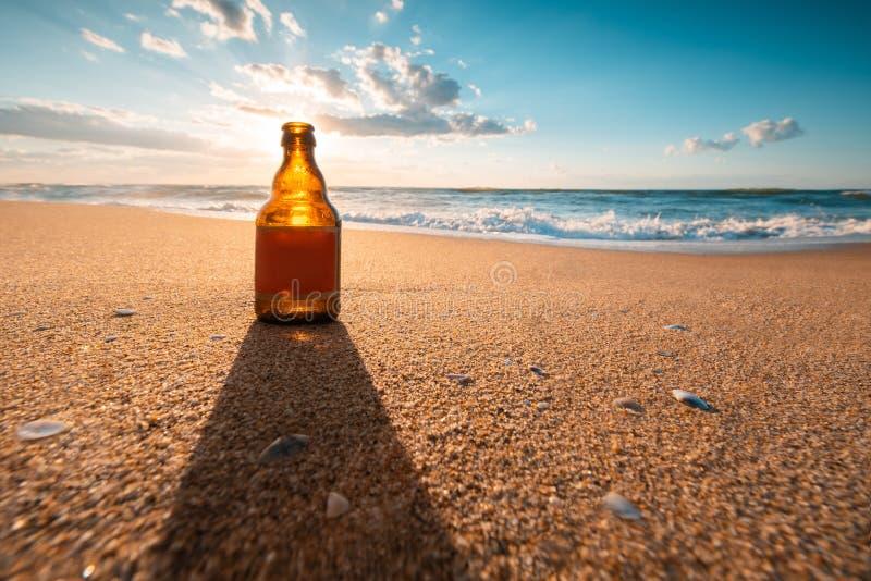 Mooie overzeese zonsopgang en bierfles op het strandzand stock fotografie