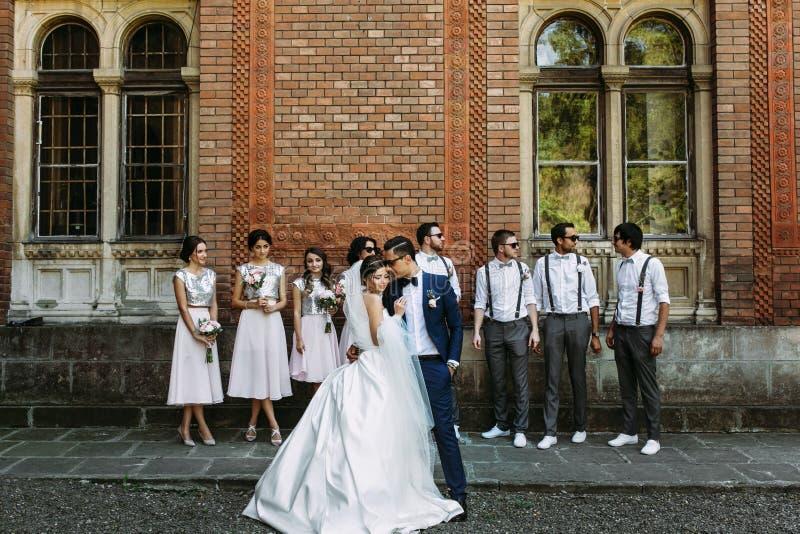 Mooie paar en bruidsmeisjes met erachter groomsmen stock foto