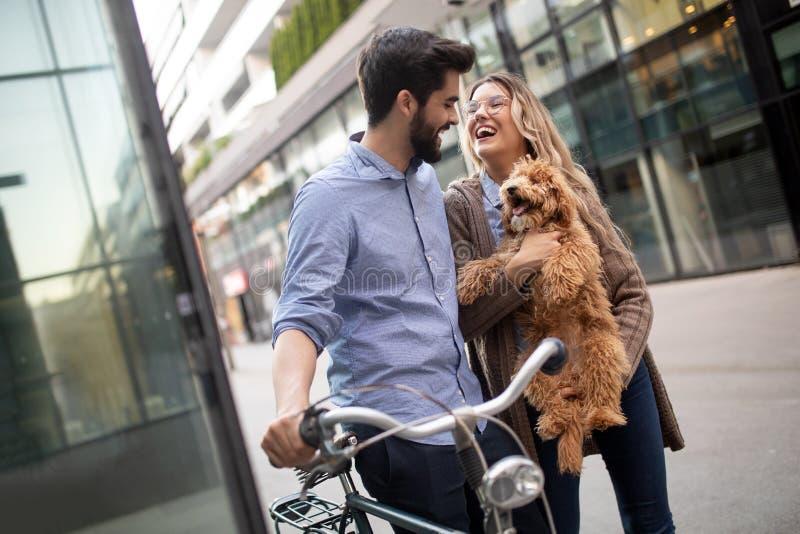 Mooie paar het lopen honden en fietsen in openlucht in stad royalty-vrije stock afbeelding