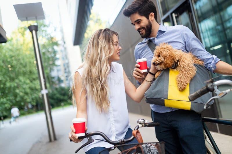 Mooie paar het lopen honden en fietsen in openlucht in stad stock afbeeldingen